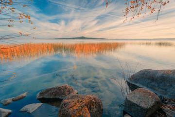 Fototapeta Rzeki i Jeziora Beautiful foggy autumnal landscape with mountain lake. Pine tree branch on foreground.
