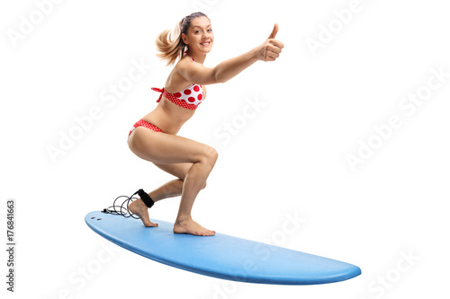 Young woman in a bikini surfing and making a thumb up gesture