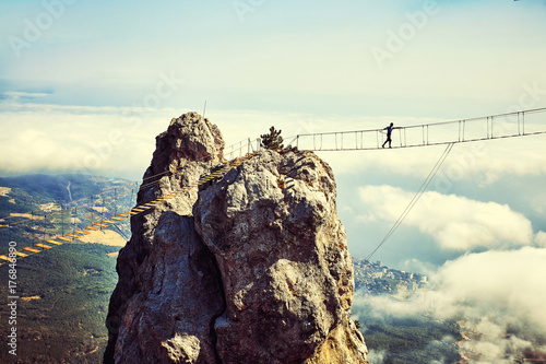 Valokuva  Woman is walking along a suspension bridge over an abyss.