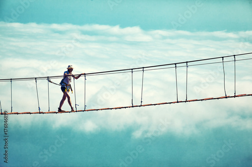 Woman is walking along a suspension bridge over an abyss.