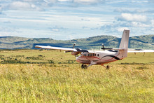 Small Passenger Propeller Plane Landed On The Green  Meadow
