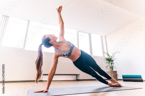 Tuinposter School de yoga Slim woman doing the side plank yoga pose