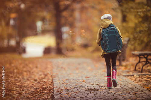 obraz PCV Travel to school. Girl walking through park. Autumn theme.