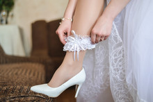 In The Morning, The Bride In Stockings And A White Wedding Dress Wears A Garter On Her Leg. On Her Legs Are Dressed Tights And White Wedding Shoes. The Bride Is Holding Her Hands For The Garter