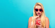 canvas print picture - Happy young woman drinking smoothie on a solid background