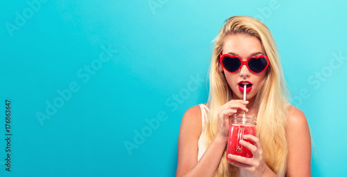 Valokuvatapetti Happy young woman drinking smoothie on a solid background