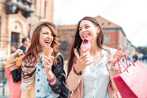 Plakat Dwie dziewczyny chodzenie z torby na zakupy na ulicach miasta.