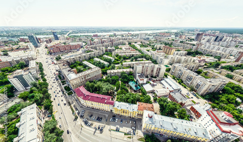 Fototapeta Aerial city view with crossroads and roads, houses, buildings, parks and parking lots, bridges. Helicopter drone shot. Wide Panoramic image. obraz na płótnie