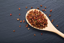 Chinese Pepper, Sichuan Pepper In Wooden Spoon On Black Slate Stone Plate With Copy Space