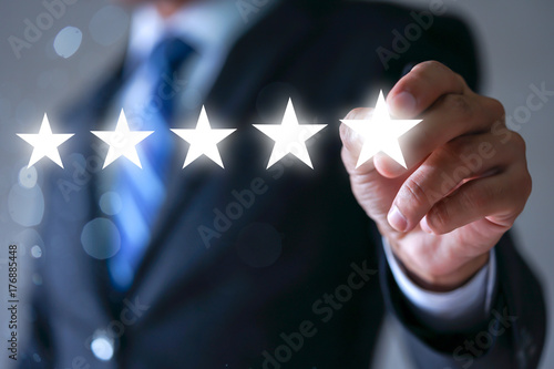Fotografía  Businessman pointing five star symbol to increase rating of company