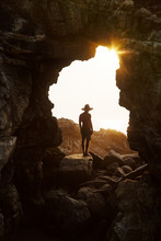 Rear View Of Man Standing In Cave Watching Sunset