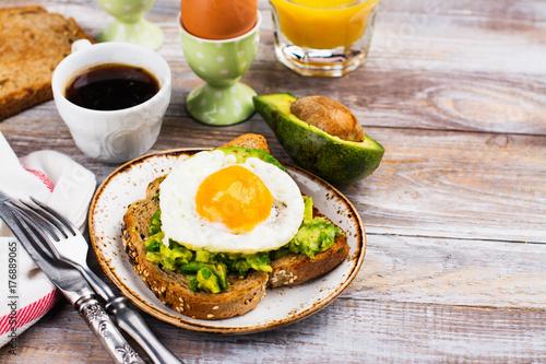 Plakat Avocado jajeczna kanapka z całym zbożowym chlebem na drewnianym tle. Skopiuj miejsce