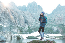 Young Happy Traveling Woman With Backpack, Hat Standing On Rock And Chating On Mobile Phone In The Stunning Mountain Wilderness In Front Of Amazing Cold Lake.