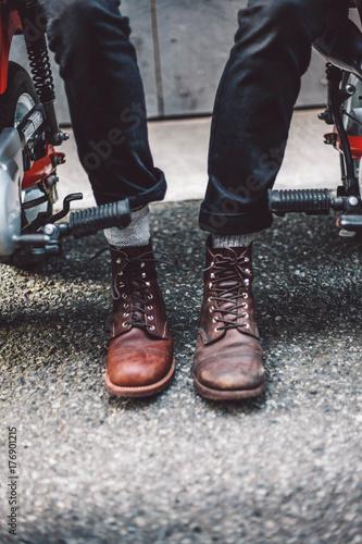 Staande foto Dragen Two young men wearing boots on motorcycle
