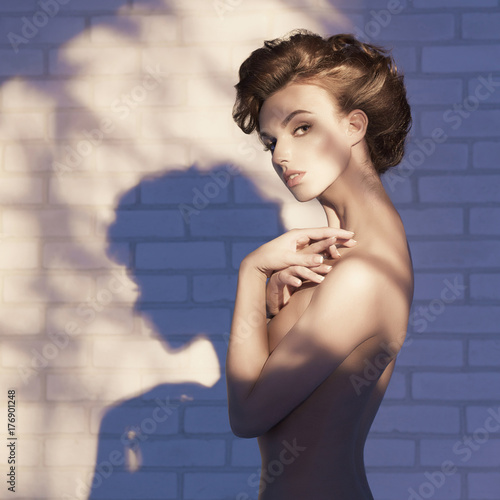 Poster womenART Nude elegant woman near the brick wall