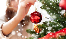 Close Up Of Woman Hand Decorating Christmas Tree