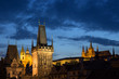 View of lit Lesser Town Bridge Towers, St. Nicholas Church and Prague (Hradcany) Castle at the Mala Strana (Lesser Town) in Prague, Czech Republic, in the evening. Copy space.