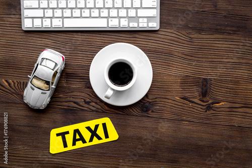 Zdjęcie XXL zadzwoń do taksówki z app, klawiatury i filiżankę kawy drewniany stół tło widok z góry lato