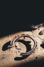 Rusty Old Horseshoe In Bright Light With Strong Shadow