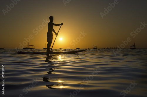 Plakat Sylwetka mężczyzna paddling na paddle desce przy zmierzchem.
