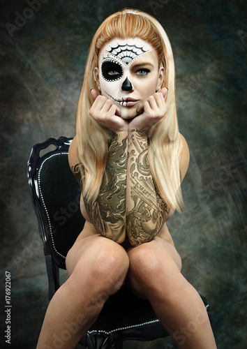 Front portrait of a sitting semi nude female with skull makeup and