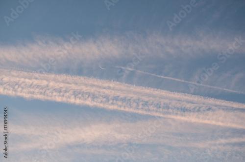 Photo trainées d'avions au petit matin avec un joli croissant de lune