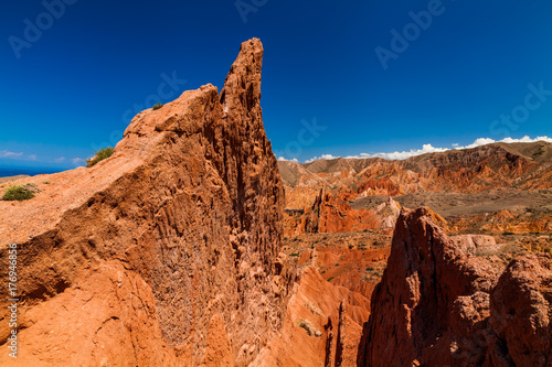 Staande foto Oranje eclat Red rocks under the blue sky in the canyon Skazka, Kyrgyzstan