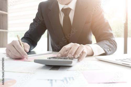 Finance concept,finance control audit man calculate business financial data on calculator.