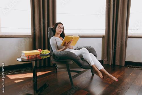 Plakat Piękna młoda kobieta w domu siedzi na nowoczesne krzesło przed oknem, relaksując się w jej salonie i czytanie książki