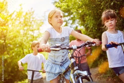 Fototapeta Latem dzieci jeżdżą na rowerach i hulajnogach