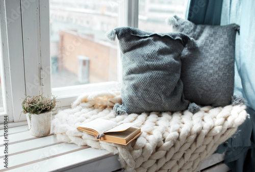 Fotografija  Warm and cozy window seat with cushions and a opened book, light through vintage shutters, rustic style home decor