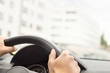 Man driving car in city. Driver holding steering wheel with both hands. Road trip, travel or commute concept. Buildings in the blurred background.