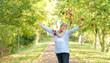 Seniorin voller Lebensfreude im Herbst