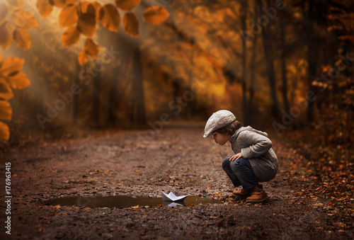 Poster Marron chocolat Little boy playing with the paper boat in the autumn forest puddle