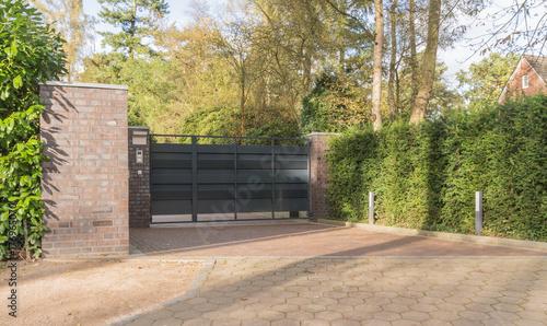 Fotografía  Einfahrt eines Grundstücks mit einem Tor in anthrazit