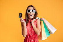 Close-up Of Happy Exited Brunette Woman In Sunglasses Holding Credit Card And Colorful Shopping Bags, Looking At Camera
