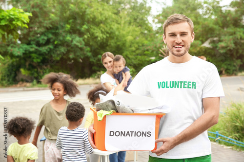Fotografía  Young male volunteer holding box of donations outdoors