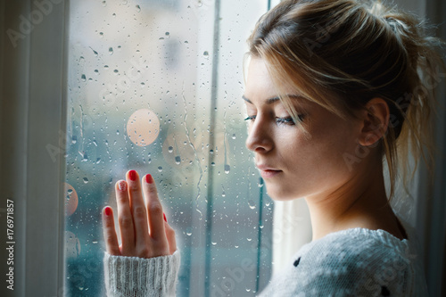 Fotografía  Young girl looking out the window and feeling sad
