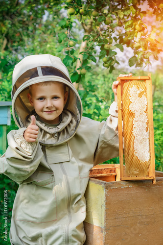 A boy beekeeper at the hive holds a honeycomb with honey in his hands Canvas Print