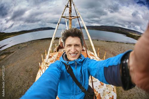 man tourist make a selfie photo on Gardar BA 64 ship wreck in
