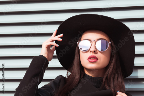 Plakat Zbliżenie portret młody uwodzicielski model jest ubranym kapelusz i okulary przeciwsłonecznych. Kobieta pozuje przy tłem żaluzje w słonecznym dniu