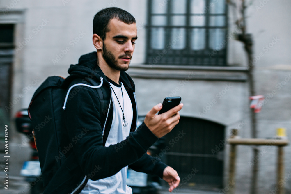 Fototapety, obrazy: Motion blur photo of handsome young man running late towards meeting or date, looks at phone to check time or timetable, runs fast to get to train station or airport
