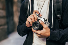 Closeup Of Man In Hipster Outfit, Black Hoodie Cardigan And White Tshirt, Holding Vintage Analog Film Camera, Zooming And Focusing