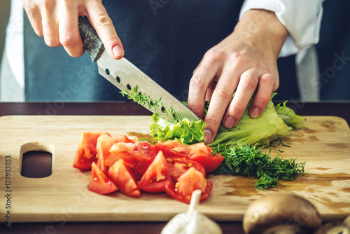 The chef in black apron cuts vegetables Fotobehang
