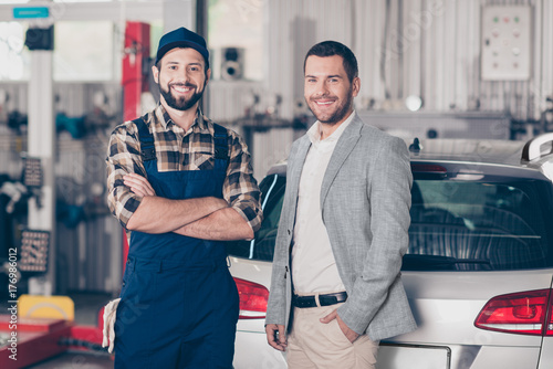 Fototapety, obrazy: Closeup of two attractive guys, cheerful specialist repairman in blue overall, businessman in formal wear, man`s property silver car. Vehicle breakdown, check, inspection, engineering concept