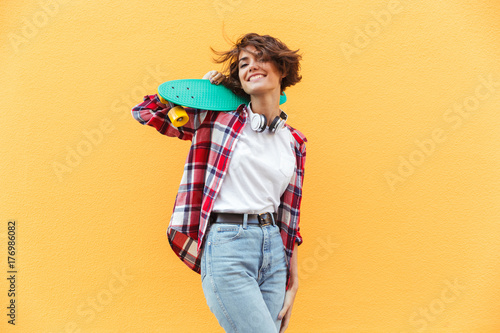 Cheerful young teenage girl holding skateboard on her shoulders
