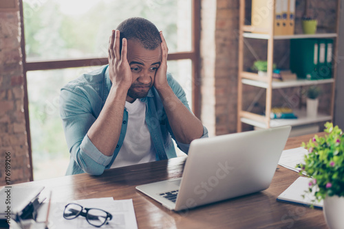 Frustrated young african entrepreneur with sad grimace in front of his laptop in Canvas Print
