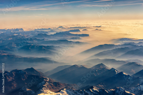 Foto auf Leinwand Gebirge Top view from airplane, Beautiful view on the mountains from the top through the clouds.