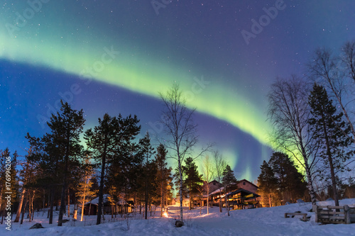 Green Northern lights belts in a blue sky over a cottage in the lapland forest