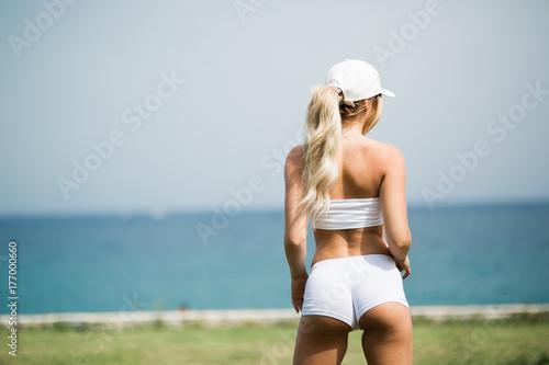 Zdjęcie XXL Seksowna i dysponowana blondynki dziewczyna stoi na brzeg i ogląda przy morzem